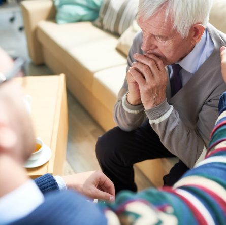 Young psychiatrist in sweater touching shoulder of sad depressed elderly patient and consoling him at therapy session